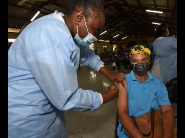 Gloria Roberts was the first person to get the COVID-19 jab from midwife Odene Wynter (left) when vaccination restarted shortly before 3 p.m. on Tuesday at the Holy Trinity Anglican Church in Linstead, St Catherine. The centre ran out of vaccines early in