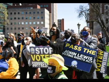 In this Tuesday, April 13 photo, people rally outside of the Capitol in Lansing, Michigan, during a rally to support voting rights and end voter suppression.