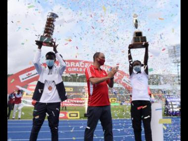Team captains J'Voughnn Blake (left) of Jamaica College, and Ackelia Smith (right) of Edwin Allen hold their trophies aloft after victories in the ISSA/GraceKennedy Boys and Girls' Athletics Championships at the National Stadium in Kingston yesterday.