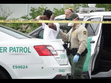 United States Border Patrol officials detain one of 14 migrants who came ashore on the intracoastal waterway in Pompano Beach, Florida, on Thursday. Several of them are believed to be Jamaicans.