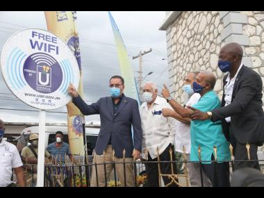 In this file photo, Minister of Science, Energy and Technology Darly Vaz, unveils a Free Wifi sign at the launch of the Universal Service Fund (USF) Free public WiFi in May Pen, Clarendon in November 2020. He was accompanied by (from left)  Member of Parli