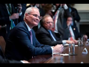 In this file photo, ExxonMobil CEO Darren Woods, at left, listens during a meeting with energy sector business leaders in the Cabinet Room of the White House in Washington. AP