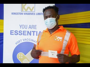 A Kingston Wharves Limited employee displays his vaccination card after receiving the jab during the recent vaccine blitz.