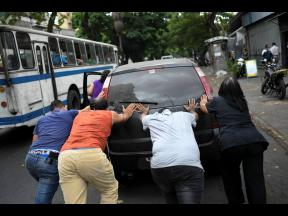 People push a car that ran out of gas to a state-run oil company PDVSA filling station in Caracas, Venezuela, yesterday. The first of five tankers loaded with gasolene sent from Iran this week is expected to temporarily ease Venezuela's fuel crunch while defying Trump administration sanctions targeting the two US foes.