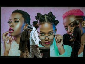 Men in face masks walk past a hair product billboard on the street in Soweto, South Africa. The coronavirus pandemic has fractured global relationships as governments act in the interest of their citizens first, but John Nkengasong, Africa's top public h