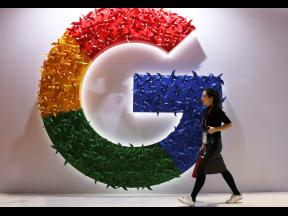 In this November 5, 2018 photo, a woman walks past the logo for Google at the China International Import Expo in Shanghai. Google says it's making progress on plans to revamp Chrome user tracking technology.