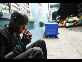 Lionel Johnson, 47, lights a cigarette while sitting outside the Kingston and St Andrew Municipal Corporation temporary night shelter on Church Street. Deported from New York almost two decades ago, Johnson said he has no relatives here in Jamaica. He said