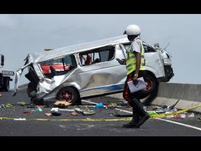 A policeman walks by the Toyota Hiace minibus that was involved in a crash on Highway 2000 on Monday.  Five people were killed in the collision.