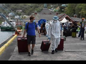 A healthcare worker helps an evacuee with his luggage as British, Canadian and U.S. nationals wait to board the Royal Caribbean cruise ship Reflection, in Kingstown, St Vincent, on Friday, April 16.