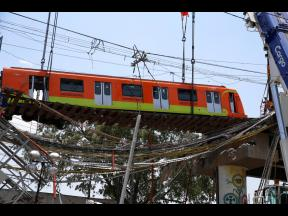 A subway car is prepared to be lowered to the ground, with the help of a crane, from a collapsed elevated section of the metro, in Mexico City. The elevated section of the Line 12 metro collapsed late Monday, killing at least 24 people and injuring at leas