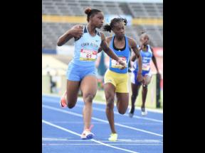 Tina Clayton (left) from Edwin Allen wins the Class Two Girls' 100 metres final in 11.38 seconds ahead of Kerrica Hill (centre) from Hydel, 11.61 seconds, at the ISSA/GraceKennedy Boys and Girls' Athletics Championships at the National Stadium yesterda