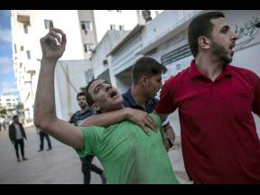 A Palestinian man reacts to the death of his father who was killed by an Israeli airstrike that destroyed the upper floors of a commercial building and caused damage to the nearby Health Ministry and prime health care clinic, in Gaza City, yesterday.