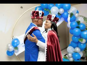 The royal couple Bartov and Latoya lean in for a nuptial kiss.