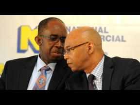 NCB Financial Group President & CEO Patrick Hylton and Deputy CEO & CFO Dennis Cohen, consult during the banking group's 2015 annual general meeting.