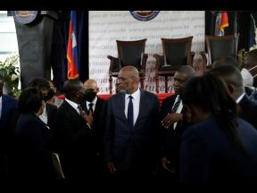 In this July 20 file photo, Prime Minister Ariel Henry (centre) talks with former Interim Prime Minister Claude Joseph as they stand surrounded by Henry's cabinet after his appointment in Port-au-Prince, Haiti, weeks after the assassination of President
