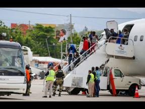 Haitians who were deported from the United States deplane at the Toussaint Louverture International Airport, in Port au Prince, Haiti, yesterday.