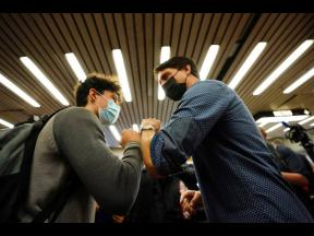 Prime Minister Justin Trudeau (right), greets commuters at a Montreal Metro station on yesterday.