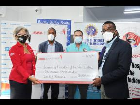 Kim Mair (left), CEO of JMMB Joan Duncan Foundation, presents a symbolic cheque valued at $1.7m to the University Hospital of the West Indies (UHWI) field hospital during a handover event at the 48-bed facility. Captured in the photo (from second left) are