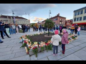 People gather around flowers and candles after a man killed several people on Wednesday afternoon in Kongsberg, Norway.