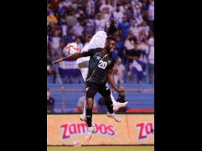 Jamaica's Kemar Lawrence (front) and Honduras' Alberth Elis, jump for a header during their FIFA World Cup qualifying match at Estadio Olímpico Metropolitano in San Pedro Sula, Honduras on Wednesday.
