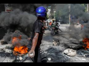 A protester threatens to throw stones at motorists trying to pass a roadblock set by anti-government protesters in Port-au-Prince, Haiti, yesterday. Demonstrators decry a severe fuel shortage and a spike in insecurity as they demanded that Prime Minister A