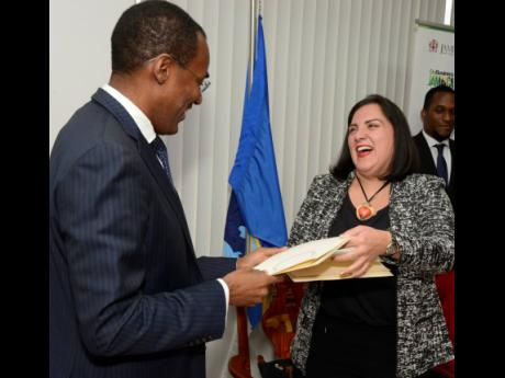 Nigel Clarke (left), minister of finance and the public service, exchanges documents with Adriana La Valley, chief of operations at the Inter-American Development Bank, at a signing ceremony for the Skills Development for Global Services loan contract between the Government  the bank. The  signing took place at the Ministry of Finance and the Public Service's Heroes Circle offices yesterday.