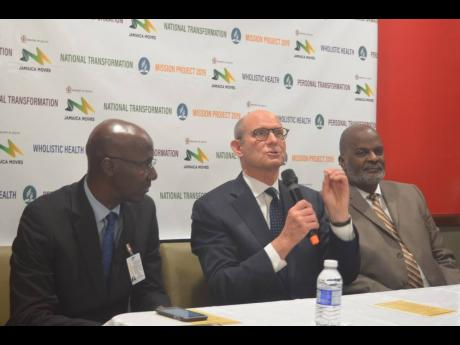 Pastor Ted Wilson (second left), president of the General Conference of Seventh-day Adventist Churches, leads a brief prayer during a press conference at Sangster International Airport in Montego Bay, St James, yesterday. Also pictured are Pastor Everett Brown (left), president of the Jamaica Union Conference, and Pastor Ellie Henry, president of the Inter-American Division of Seventh-day Adventists.