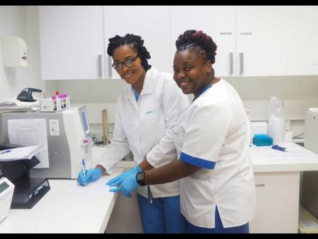 Laboratory supervisor  Elizabeth Graham (left) and phlebotomist, Angella Stephens providing service with a smile at Hospiten in Montego Bay, St James.
