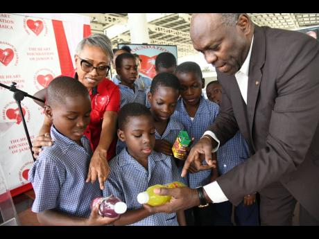 Fitzroy Henry, professor of public health nutrition at the University of Technology (UTech), and consultant cardiologist Dr Andrene Chung, chairman of the Heart Foundation of Jamaica (HFJ), chat with students from Seaward Drive Primary School about sugary drinks as the Heart Foundation of Jamaica launches Phase 4 of the 'Are We Drinking Ourselves Sick?'  campaign at the Half-Way Tree Transport Centre yesterday.