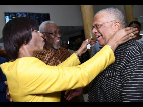 Former Prime Minister Portia Simpson Miller chats with former Prime Minister P.J. Patterson, (centre) and Opposition Leader Dr Peter Phillips at the premiere of the documentary 'Journey Break Every Rule' at the Carib Cinema yesterday.