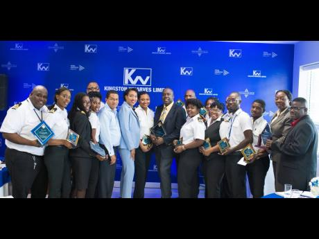 CEO of Kingston Wharves Grantley Stephenson (fifth from left) and Commissioner of Customs Velma Ricketts-Walker (sixth from left) share in the moment with  customs officers, managers and supervisors who were recognised by Kingston Wharves Limited for their services.