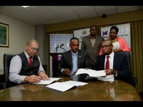 Seated (from left): Orville Hill, general manager, finance and procurement at JSIF; Omar Sweeney, managing director at JSIF; and Rohan Richards, technical director at JSIF, participate in the signing of an MOU between JSIF and the Ministry of National Security on Oxford Road, New Kingston, on Thursday. Looking on are Orette Boscoe, statistics manager, JSIF, and Shauna Trowers, acting chief technical director at the Ministry of National Security.
