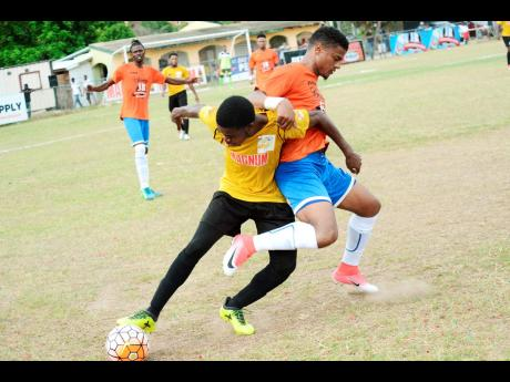 Barbican's Malik Douglas (left) and Adrian Williams of Dunbeholden FC  in a tussle for the ball during a Magnum/Charley's JB Jamaica Football Federation Premier League play-off game at the Barbican Complex last year.