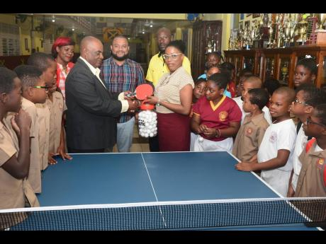 Godfrey Lothian, president, Table Tennis Jamaica, makes a presentation of table tennis racquets, balls and a table to Ms Janet Howard, principal, Wolmer's Preparatory School, at the institution yesterday. Along with curious students, others looking on (from left) are PTA President Lisa Reynolds, Board Chairman Ryan Foster and coach Raymond Leveridge.
