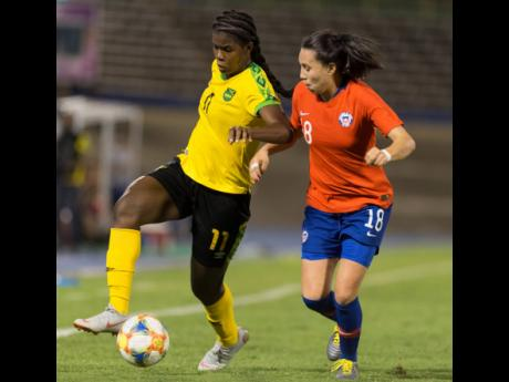 Jamaica's striker Khadija Shaw (left) dribbles the ball downfield, while being pressured by Chile's Camila Sáez during their international friendly held at the National Stadium last Thursday. Jamaica won 1-0.