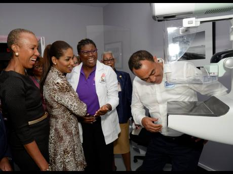 Dr Christoper Tufton (right), minister of health, playfully tries to put his chest under the 3D imaging mammograph in the Women's Imaging Centre at the UHWI yesterday to the amusement of  (from left) Fayval Williams, technology minister; Lisa Hanna, member of parliament for South East St Ann, who represented the leader of the Opposition; Dr Derria Cornwall, head of the Women's Imaging Centre; and Janet Coore-Farr, former president of the Nurses Association of Jamaica (NAJ).