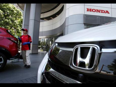 In this July 31, 2018, file photo, an employee of Honda Motor Company cleans a Honda car displayed at its headquarters in Tokyo.
