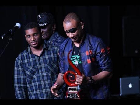 Renaissance Disco principal Delano Thomas Sr (right) receives an award at the recently held Jamaica Reggae Industry Association awards ceremony for his contribution to Jamaican music. Beside him is his son Delano Thomas Jr.