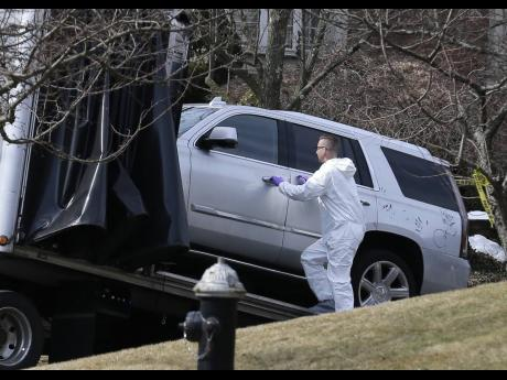 Crime scene investigators load a car that appears to have been checked for fingerprints on to a flatbed truck in the Staten Island borough of New York yesterday.  Francesco 'Franky Boy' Cali was found with multiple gunshot wounds at his red-brick, colonial-style house on Staten Island on Wednesday night and was pronounced dead at a hospital.
