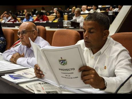 In this July 21, 2018 photo, a member of the National Assembly studies the proposed constitutional update in Havana, Cuba.