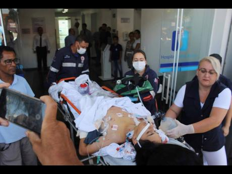 A teenager who was injured during the shooting at Raul Brasil State School is carried on a gurney into a hospital in Suzano, Brazil, on Wednesday, March 13.