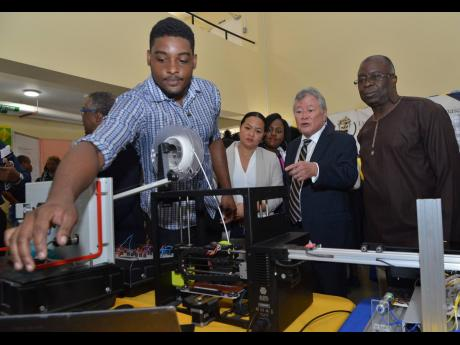 André Craig, of the Department of Mechanical Engineering, explains the use of his 3D printer to Gary 'Butch' Hendrickson (second right), chairman and CEO of Continental Baking Company; Martin Henry (right), UTech administrative manager; and Tiffany Wong, special projects officer of Continental, at the opening ceremony of Research, Technology & Innovation Day on Thursday.