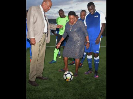The Minister of Culture, Gender, Entertainment and Sport, Olivia Grange (centre), controls the ball on the new turf at the UWI/JFF Captain Horace Burrell Centre of Excellence. Looking on are  (from left) President, Jamaica Football Federation, Michael Ricketts; former national footballers, Loxlye Reid; Lenworth 'Lenny' Hyde; and Theodore 'Tappa' Whitmore, who currently serves as the national head coach.