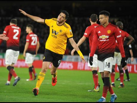 Wolverhampton's Raúl Jiménez  (centre) celebrates after scoring his side's opening goal during the English FA Cup quarterfinal match against Manchester United at the Molineux Stadium in Wolverhampton, England, yesterday. Wolverhampton won 2-1.