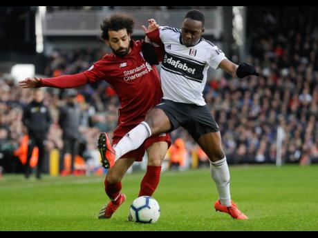 Liverpool's Mohamed Salah (left) and Fulham's Neeskens Kebano vie for the ball during their English Premier League match at Craven Cottage stadium in London, yesterday. Liverpool won 2-1.