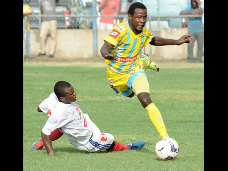 Damarley Samuels (right) from Waterhouse is about to be taken down with a hard sliding tackle from Kemar Phillipott from Portmore United during a Red Stripe Premier League match at the Waterhouse Stadium in 2015.