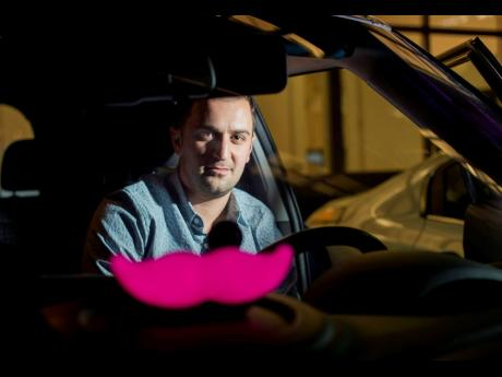 In this January 26, 2015, file photo, Lyft co-founder John Zimmer displays his company's 'glowstache' following a launch event in San Francisco.
