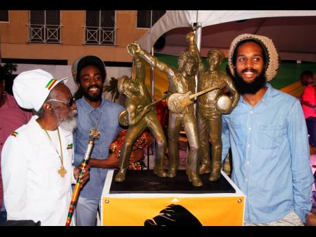 Bunny Wailer (left) his son, Abijah 'Asadenaki' Livingston (second left), and Andre 'Dre' McIntosh, the grandson of Peter Tosh, pose with the maquette for the Wailers statue.