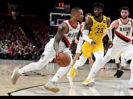 Portland Trail Blazers guard Damian Lillard (left) drives to the basket on Indiana Pacers guard Wesley Matthews during the second half of an NBA basketball game in Portland on Monday night. The Blazers won 106-98.