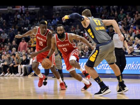Houston Rockets guard James Harden (13) drives between teammate Clint Capela (15) and Memphis Grizzlies centre Jonas Valanciunas (17) during the second half of an NBA basketball game on Wednesday night in Memphis, Tennessee. The Grizzlies won 126-125 in overtime.